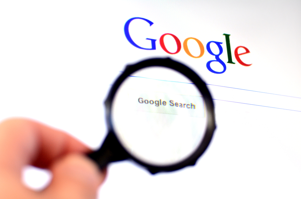 AUCKLAND - AUG 10 2014:Hand holds Magnifying glass against Google homepage.620 million users visit www.google.com daily, almost all the people who use the Internet every day.